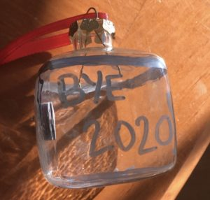 """A glass ornament has """"Bye 2020"""" written on it with silver sharpie"""