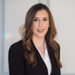 Courtney Reigel Meet Associate Attorney Courtney Reigel headshot wearing black and white and smiling into camera